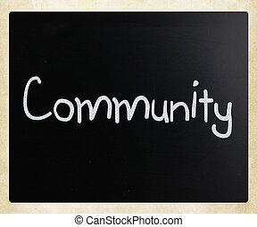 """Community"" handwritten with white chalk on a blackboard"