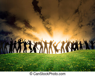 Community - many happy people are dancing on the grass