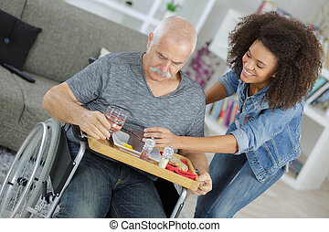 community nurse with old disabled man on wheelchair