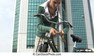 commuter - woman locking padlock to her bike. 30 fps