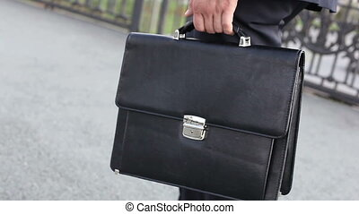 Commuter - Close-up of a commuter with a briefcase crossing...