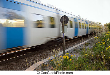 Commuter train at full speed in a rural area