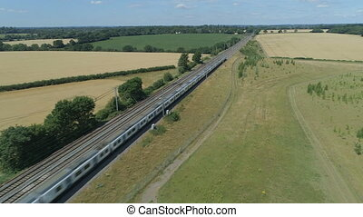 Commuter Train Speeding Through the Countryside in Summer -...