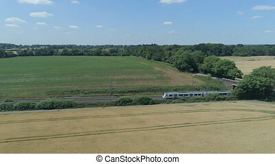 Commuter Train Speeding Through the Countryside in Summer -...