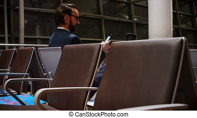 Commuter using mobile phone in waiting area 4k - Commuter...