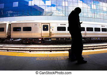 Commuter with Cellphone - Silhouetted figure holding a cell...