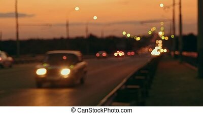 Commuters traffic on the night road in front of sunset sky