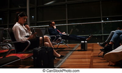 Commuters using mobile phone and laptop in waiting area 4k -...