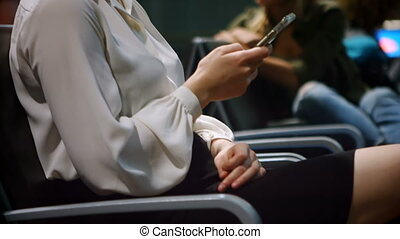 Commuters using mobile phone in waiting area 4k - Commuters...