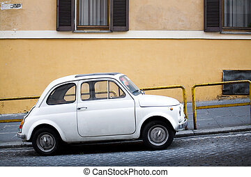 Compact car parked on a small uphill Italian street