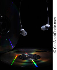 compact disk and white headphones on a dark background. listening to music on cd disc