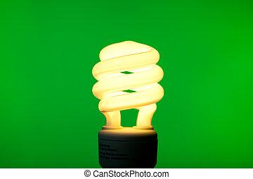 A compact flourescent bulb on a green background - energy saving, environmental theme