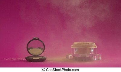 Compact powder box and jar with crumbly powder in the frame....