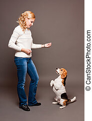 Portrait of a beautiful young blond woman with a cute beagle.