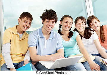 Companions - Portrait of five teens sitting with laptop, ...