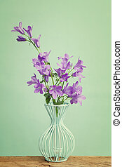 Companula flowers in a blue vase on wooden table