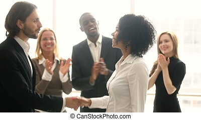 Company boss handshaking african employee, promoting congratulating black young woman