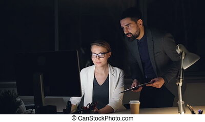 Company CEO is talking to his secretary working with computer late hours giving orders and discussing work. People are wearing formal suits and accessories.