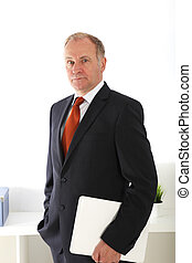 Company director standing with laptop