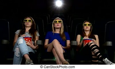 company of girl watching a movie at cinema: horror film in 3D