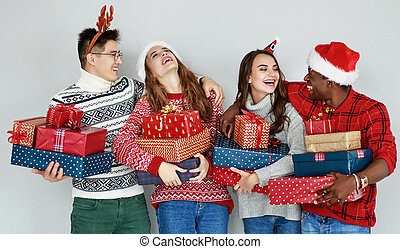 company of happy friends with Christmas gifts at empty wall