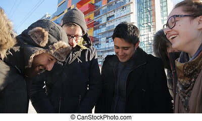 Company of happy people stands on cold winter street in day time.