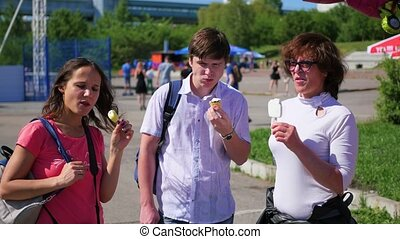 Company of people in the Park eat ice cream and talk. food outdoors