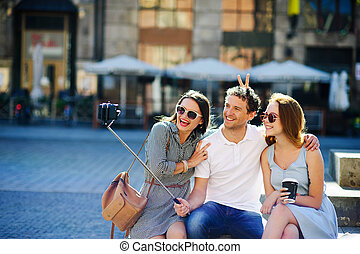 Company of young friends is photographed in the city square.