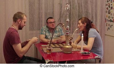 Company people smoking shisha and playing cards