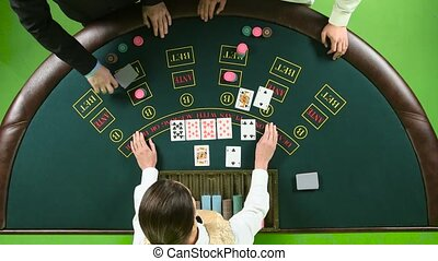 Company plays poker in casino at the table. Green screen. Top view