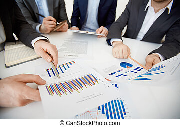 Two co-workers pointing at charts while comparing them