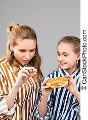 Long-haired adult woman observing her tiny fake burger - ...