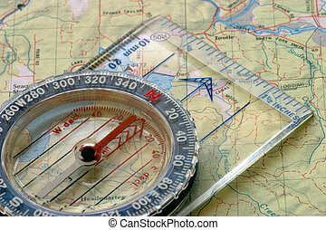Compass and Map - Close-up view of a compass sitting on a...