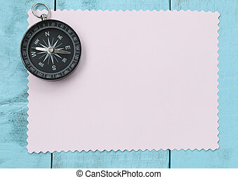Compass and note paper on the blue wooden floor.