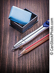 compass and pencil eraser on vintage wooden board learning conce