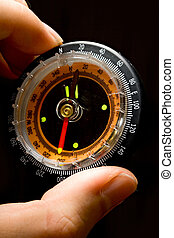 Compass in a hand on the black background