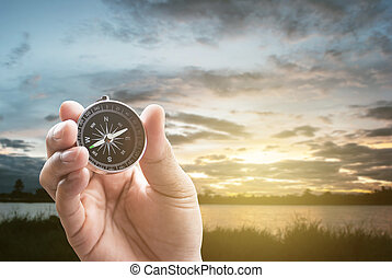 compass in hand on lagoon in the evening at sunset dark and noise background with dramatic clouds.