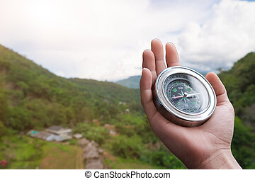 Compass in the hand on the nature background.
