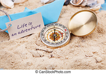 compass in the sand with sign - Life is an adventure