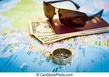 Compass, passport, money and sunglasses on the map