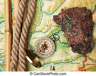 compass with a rope and a stone on topographic map