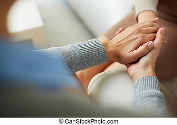 Compassion - Close-up of psychiatrist hands together holding...