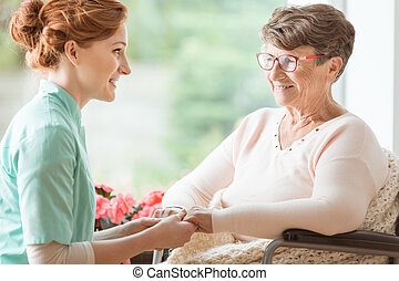 Compassionate nurse explaining a geriatric handicapped patient with dementia medical procedures while holding her hands. Assisted living house for pensioners. Side view.