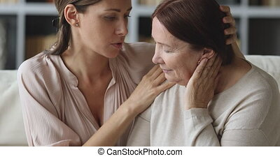 Compassionate young woman embracing shoulders of depressed middle aged mother.
