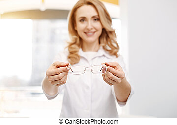 Competent capable optician holding a pair of spectacles