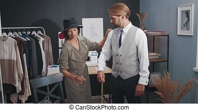 Competent fashion designer using tape for taking measurements of bearded man in business suit. Mature man visiting modern atelier for creating new outfit.