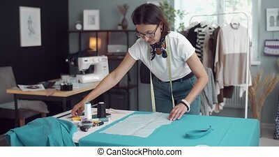 Competent female dressmaker working with paper pattern on blue fabric. Beautiful woman with brown hair measuring textile in studio for new dress.