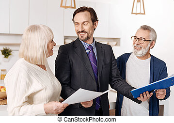 Competent legal advisor presenting contract for aged couple of clients