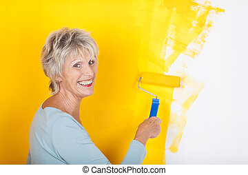 Competent senior woman painting a wall