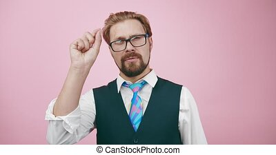 Mature bearded man in formal suit talking and gesturing on camera. Competent teacher explaining new material in studio with pink background.
